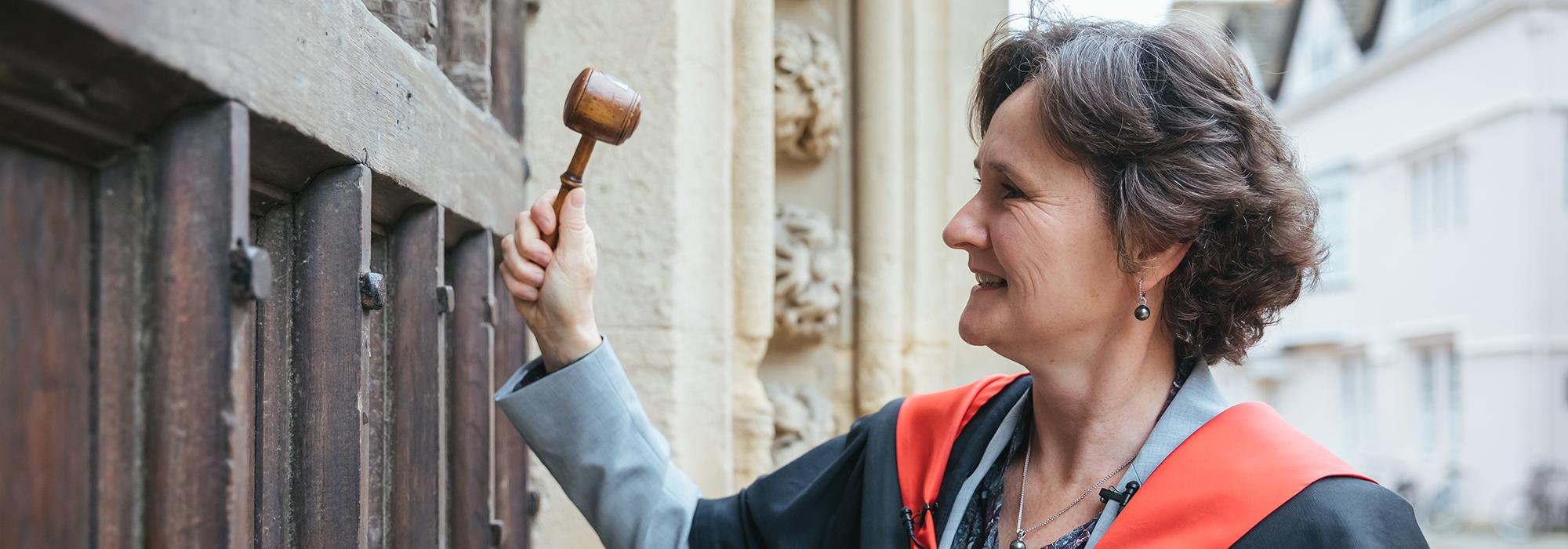 Professor Irene Tracey knocks at the gate with a gavel, prior to her ceremonial installation as 51st Warden of Merton College, Oxford - Photo © Ian Wallman