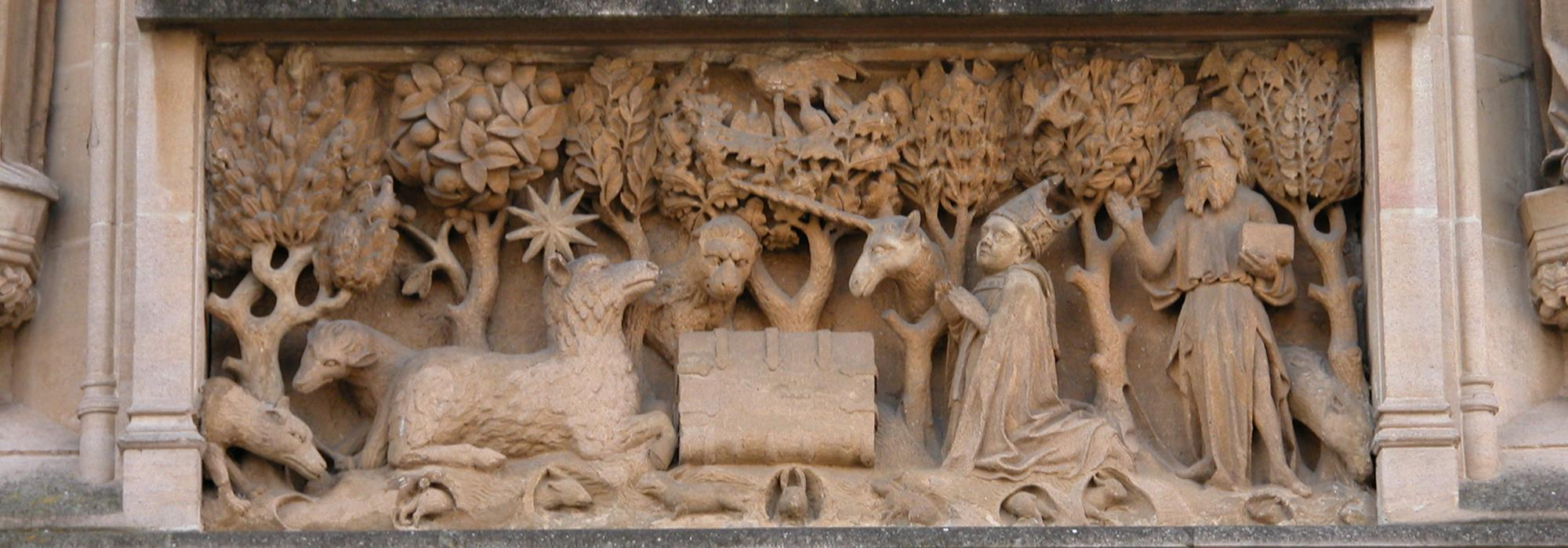 Central stone panel above the entrance to the College; it represents a book with the Agnus Dei on one side and St John the Baptist and the founder on the other side set in a landscape background with various animals.