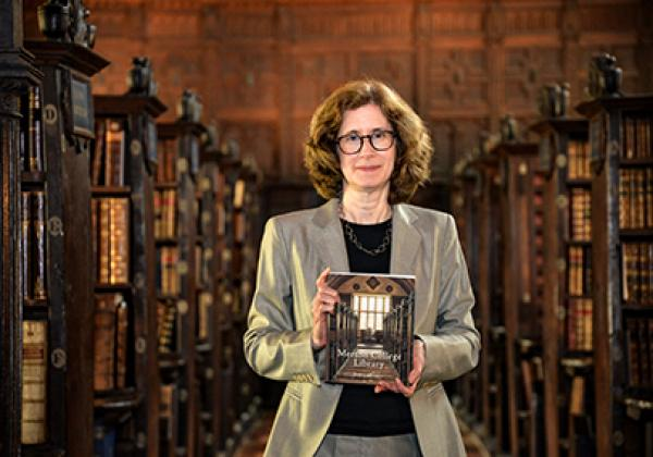 Dr Julia Walworth with a copy of her book, a history of Merton College Library, in the Upper Library - Photo: © Ian Wallman - www.ianwallman.com